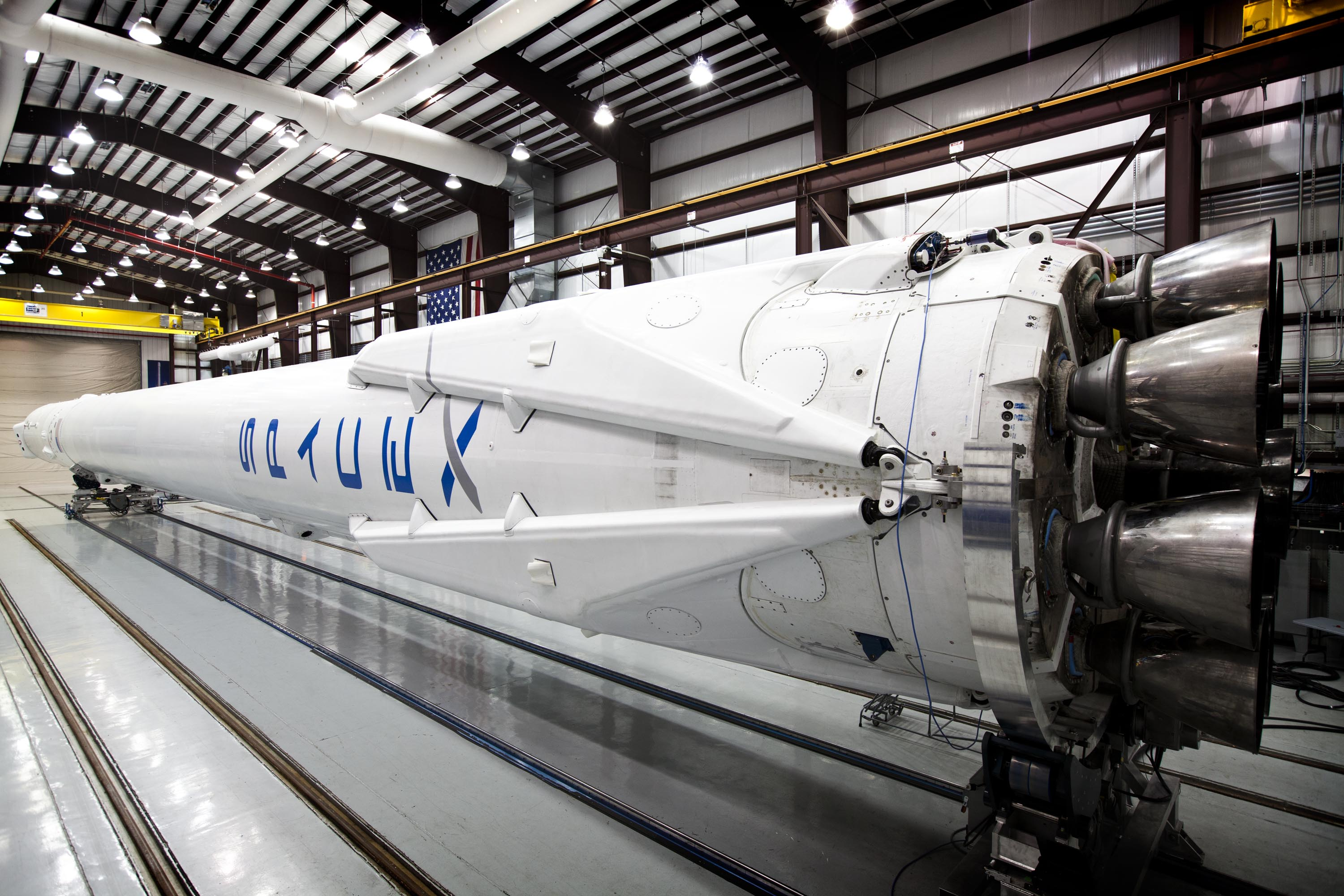 Falcon 9 in SpaceX's hangar with landing legs attached.